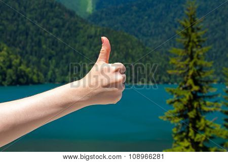 Thumb on the background of a mountain lake