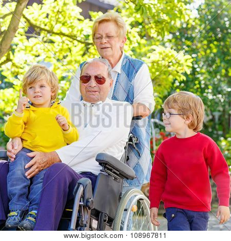 Two little kid boys, their grandmother and grandfather in wheelc