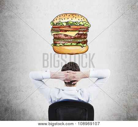 A Rear View Of Sitting Relaxing Man Who Is Dreaming About Burger. A Fast Food Concept. Concrete Back