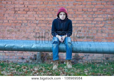 Young Homeless Boy Sits On A Pipe With Heating