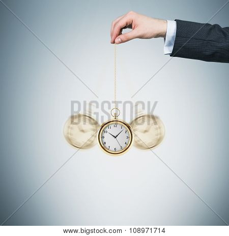 A Hand Holds A Gold Pocket Watch In A Chain As A Pendulum. Light Blue Background. Time Is Money Conc