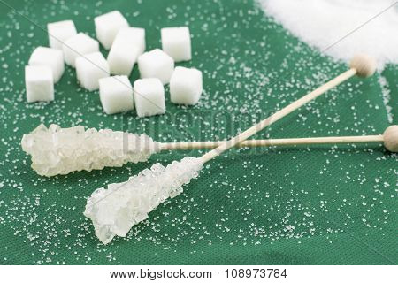 Two Sugar Sticks And Sugar Cubes On Green