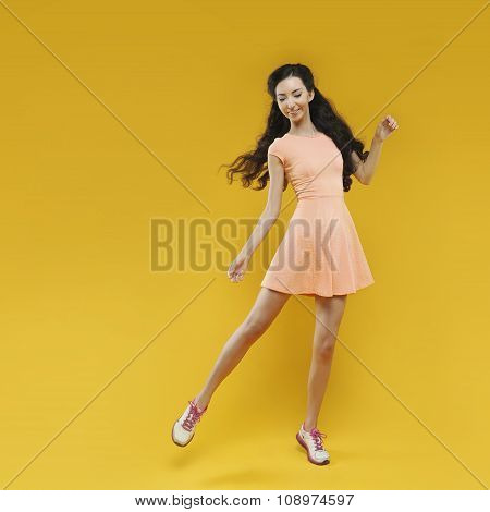 Cute asian young  girl waving to someone. Portrait on yellow background.