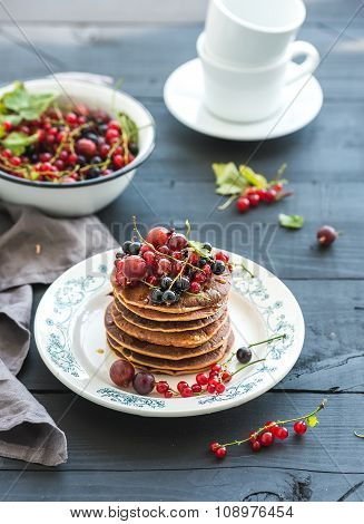 Breakfast set. Buckwheat pancakes with fresh berries and honey on rustic plate over black wooden tab