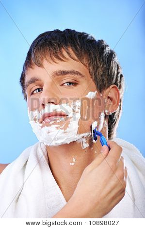 Handsome young man shaving
