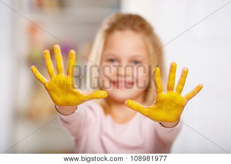Kid hands covered in yellow paint.