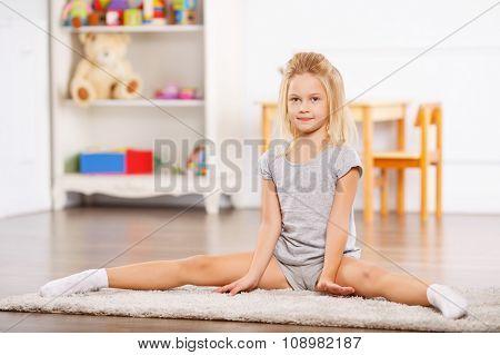 Little girl doing split on the floor.