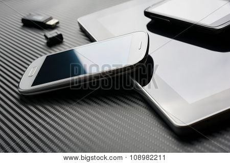 Blank Phones Lying And Leaning On Business Tablet Beside An USB Drive Above A Carbon Background