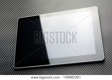 Blank Business Tablet With Reflection Lying On Carbon Background