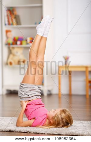 Little girl doing stretching exercises at home.