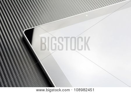 Business Tablet With Blank Screen And Reflection On Carbon Background