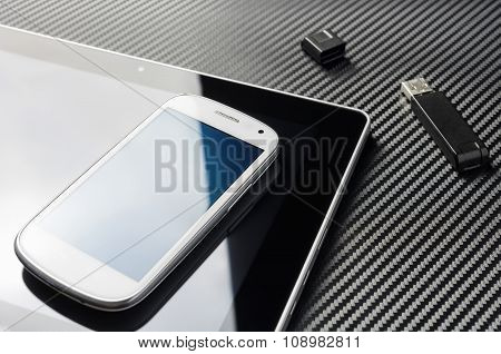White Smartphone With Reflection Lying On Business Tablet Next To An USB Device, All On Carbon Layer