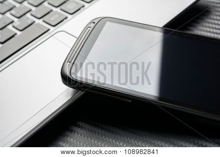 Blank Business Smartphone With Reflection Leaning On Notebook Keyboard, All Above Carbon Background