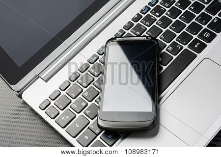 Blank Black Business Smartphone With Reflection Lying On Netbook Keyboard, All Above A Carbon Layer