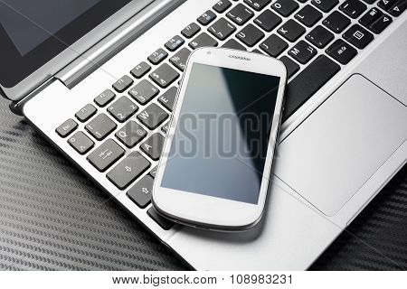 Blank Business Phone With Reflection Lying On A Notebook Keyboard With, All Above A Carbon Layer