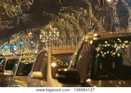Light String Decorated Trees With Cars At Christmas Night