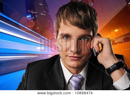 Young businessman talking on mobile phone against city background