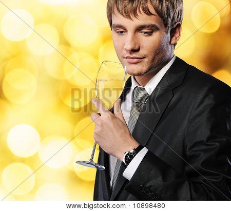 Empresario con una copa de champán sobre fondo abstracto