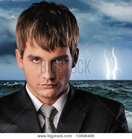 Portrait of a serious businessman over dark stormy sky