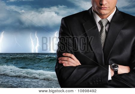 Businessman over dark stormy sky