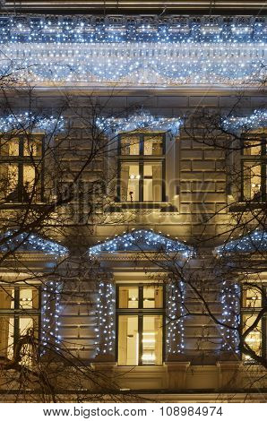Building Facade With Light Decoration At Night With Tree Bough