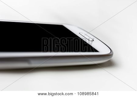 A White Handy With Blank Display Lying On White Leather