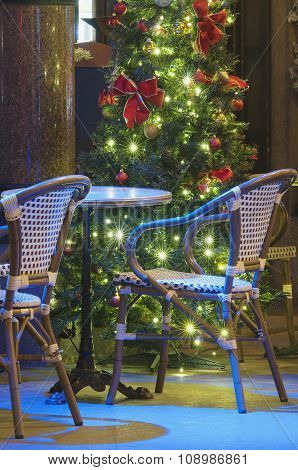 Light Decorated Christmas Tree With Empty Rattan Chairs