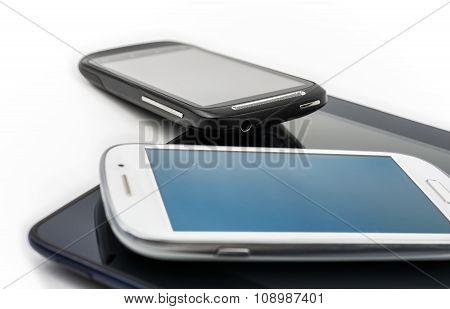 White Smartphone On Tablet & Black Mobile Leaning On Tablet