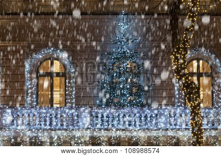 Building Facade With Light Decoration With Christmas Tree During Snowfall