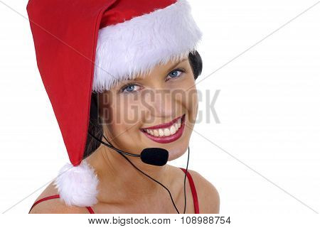 Closeup Of Attractive Female Call Center Telephonist With Telephone Headset And Christmas Hat Or San