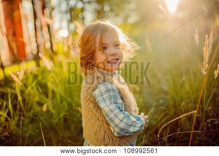Cute Smiling Girl In A Green Field In Sunset