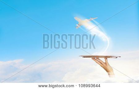 Hand of waiter holding tray with flying airplane