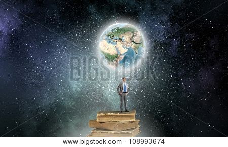 Young confident businessman with arms on waist standing on pile of old books. Elements of this image are furnished by NASA