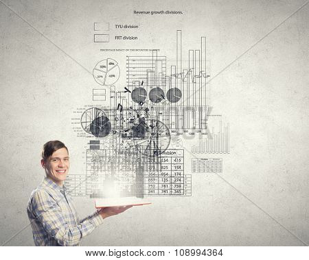 Young smiling man with opened book in hands and infographs on wall