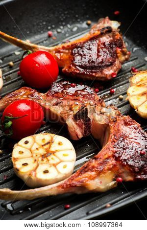 Roasted lamb ribs with spices, herbs and garlic on black cooking pan and wooden background