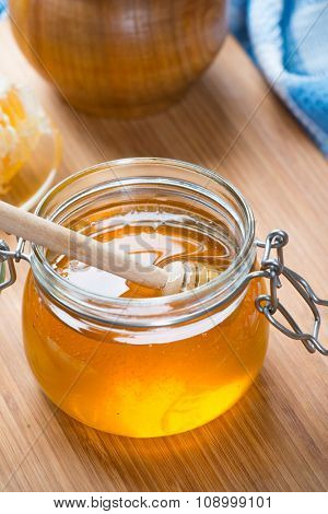 Honey in glass jar and honeycombs wax