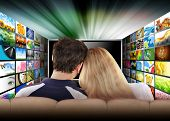 image of cuddling  - A couple is sitting on a couch watching a flat screen television with photo images coming out of the sides - JPG