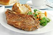 stock photo of ribeye steak  - A grilled rib eye steak with a baked potato - JPG