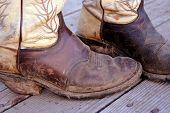 stock photo of buckaroo  - muddy cowboy boots shot on rustic wood backgound - JPG