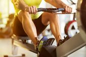 Fit man training on row machine in gym poster