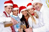 stock photo of christmas party  - Portrait of smart colleagues with flutes of champagne looking at camera - JPG