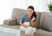 image of watching movie  - Merry woman eating pop corn while watching a movie on television at home - JPG
