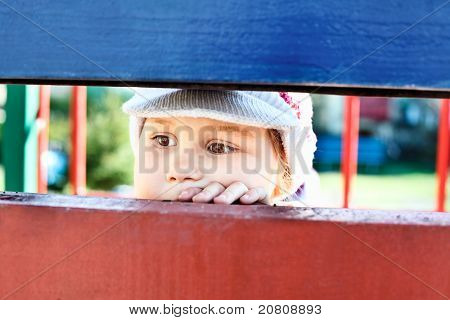 Little Child Looking Through A Crack Between Wooden Planks