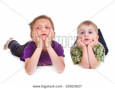 Dois miúdos entediados, deitado sobre o branco