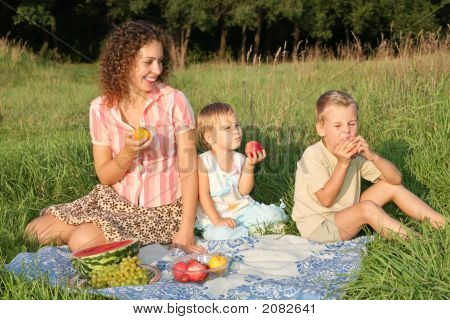 Mother And Children Eat Fruits