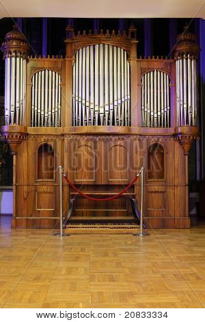 Massive wooden pipe old organ with many metal pipes and ornate finishing