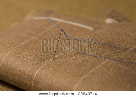 Needle And Thread On Fabric Background