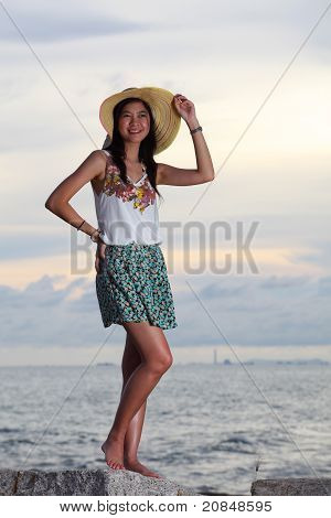 Beautiful Woman In Dress Standing On Rock Over Sea