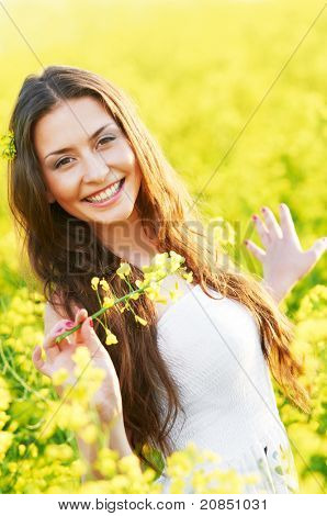 Happy smiling young woman with flower bouquet over yellow green rape meadow