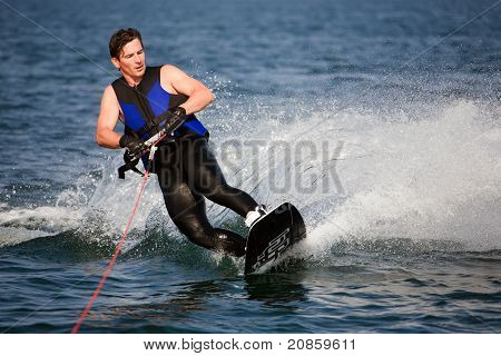 wake-boarder on water surface generating lot of splash